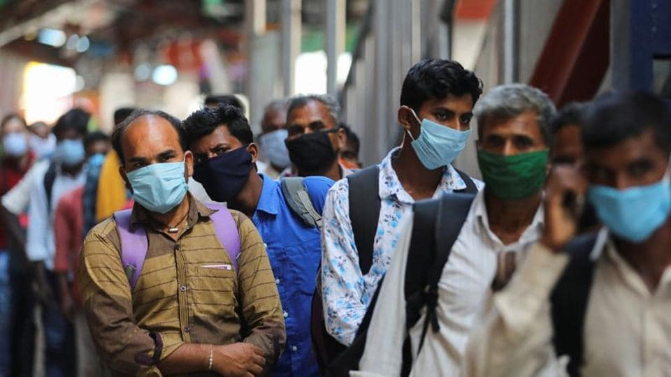 Passengers wearing protective face masks stand in a queue on a platform to get tested for the coronavirus disease (COVID-19), at a railway station in New Delhi in this file photo.
