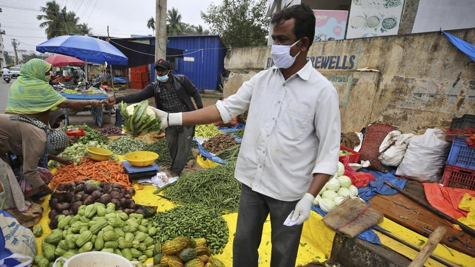 A vegetable vendor wearing gloves and face mask as a precaution against the coronavirus interacts with a customer in Bengaluru.