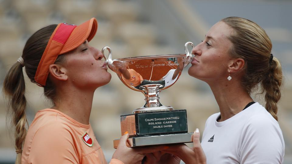 Hungary's Timea Babos,left, and France's Kristina Mladenovic hold the trophy after winning the women's doubles final match of the French Open tennis tournament against Chile's Alexa Guarachi and Desirae Krawczyk of the U.S. at the Roland Garros stadium in Paris, France, Sunday, Oct. 11, 2020.