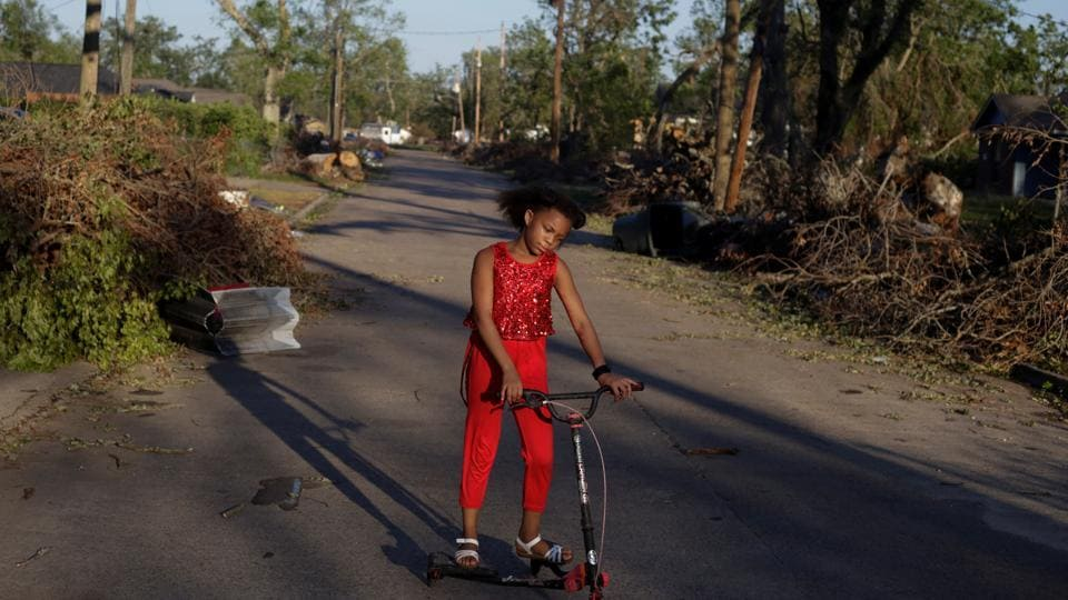 Iyana Sells, 9, plays on her street which is still lined with debris from Hurricane Laura the day after Hurricane Delta swept through Lake Charles in Louisiana on October 10.  (Kathleen Flynn / Reuters)
