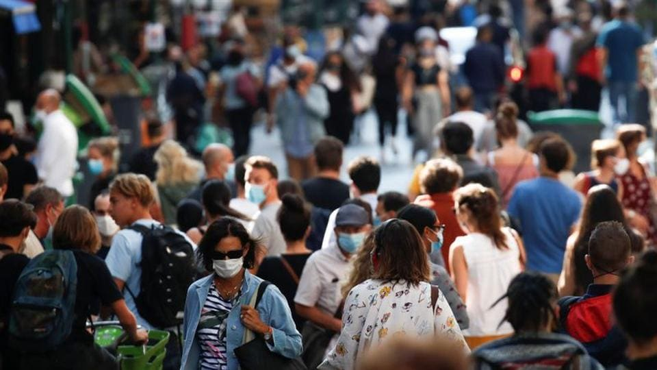 People wearing protective face masks walk in a busy street in Paris as France reinforces mask-wearing in public places as part of efforts to curb a resurgence of Covid-19.
