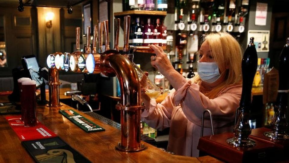 A woman wearing a face mask seen at work at the Grapes pub in Liverpool on October 12. The British government has announced a support package to pay two-thirds of the salaries of employees of companies that are told to close, but many in the pub and restaurant sector say that is not enough to save already struggling businesses. (Phil Noble / REUTERS)
