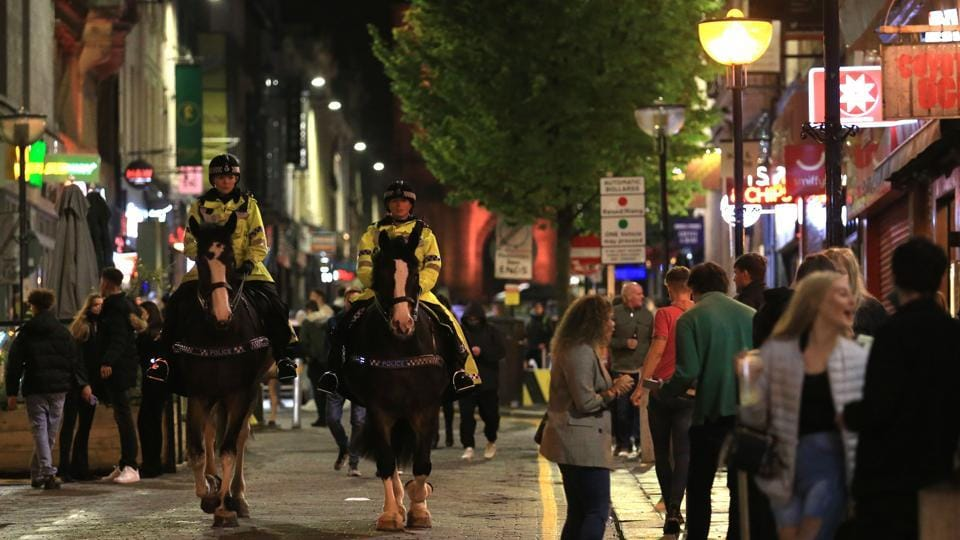 Police patrol as revellers enjoy a night out in the centre of Liverpool on October 10. Areas in the lowest tier will follow existing national restrictions, including a 10pm curfew on pubs and restaurants and a ban on more than six people gathering. In areas at high risk, members of different households are barred from meeting indoors. (Lindsey Parnaby / AFP)