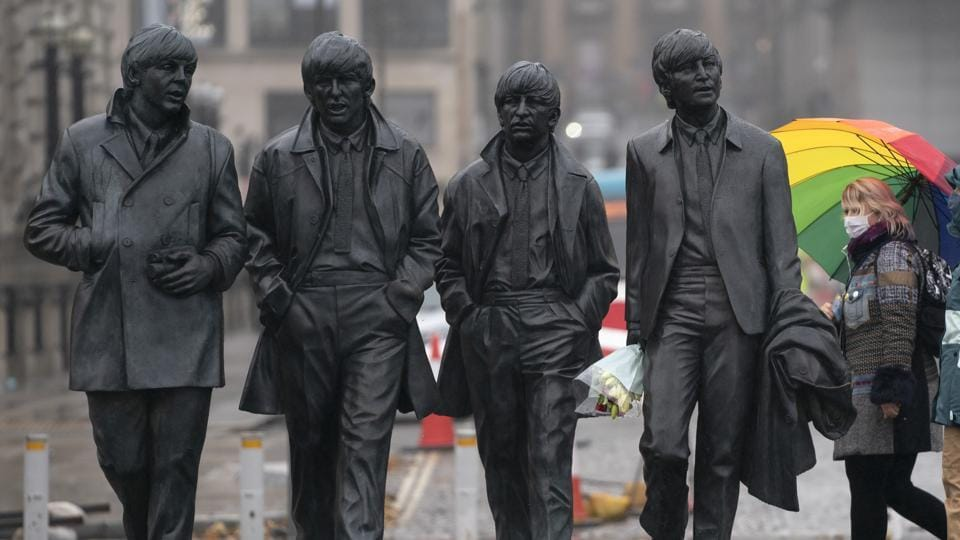 "A commuter wearing a face mask passes a statue of The Beatles in Liverpool on October 12. Liverpool was the only area put into the ""very high"" risk category on October 12, but Johnson said authorities were still talking with other local leaders across the north of England, AP reported. (Jon Super / AP)"