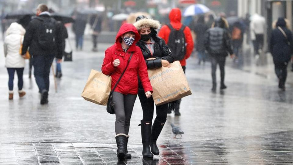 Commuters wearing face masks seen carrying shopping bags in Liverpool on October 12. Under the new measures, areas in England are classified at medium, high or very high risk, and placed under restrictions of varying severity. (Phil Noble / REUTERS)