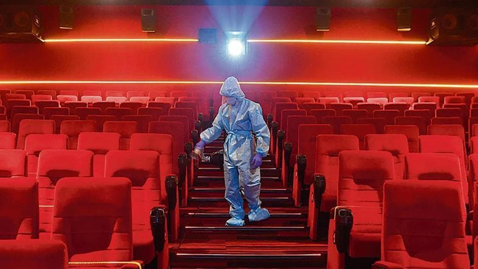 A worker sanities inside a theatre hall ahead of the scheduled reopening of cinema theatres on October 15 as the Covid-19 coronavirus imposed lockdown eases further in Mumbai on October 13, 2020.