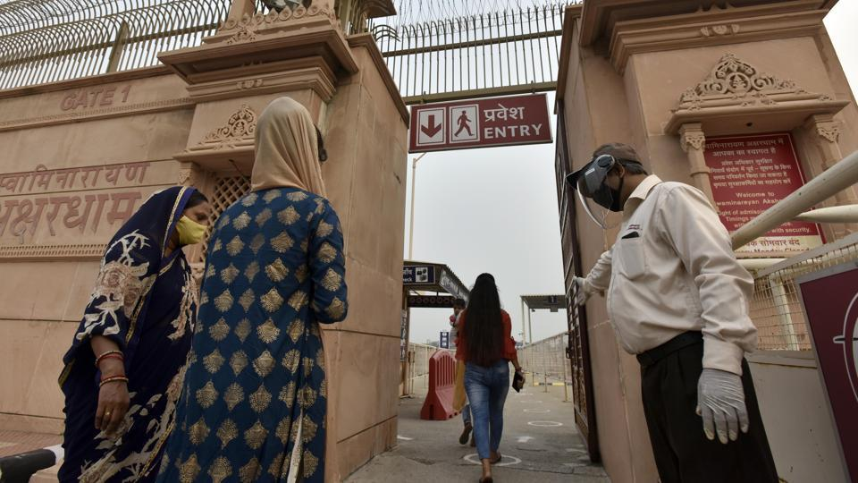 Visitors arrive to visit Akshardham Temple as it reopened after months of staying closed due to the coronavirus pandemic, in New Delhi on Tuesday.