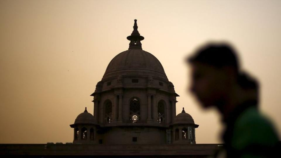 A commuter walks past the building of India's Ministry of Finance during dusk in New Delhi.