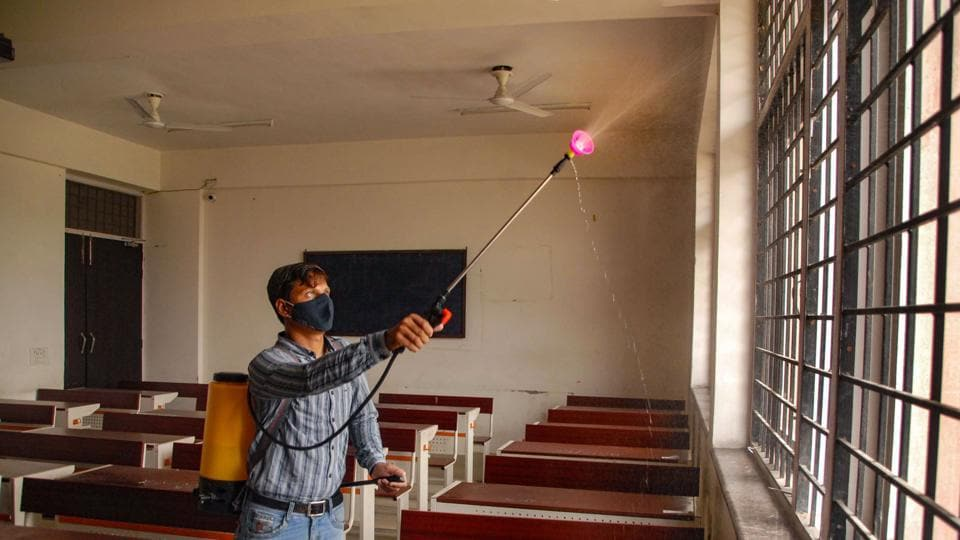 A worker sanitises a classroom at an intermediate college in Noida.