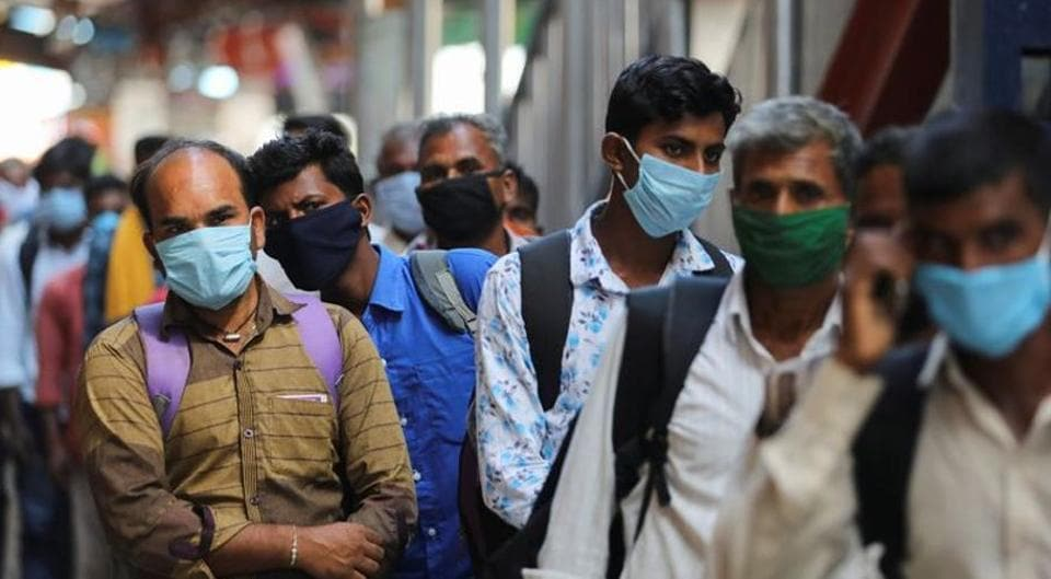 Passengers wearing protective face masks stand in a queue on a platform to get tested for Covid-19 at a railway station in New Delhi.