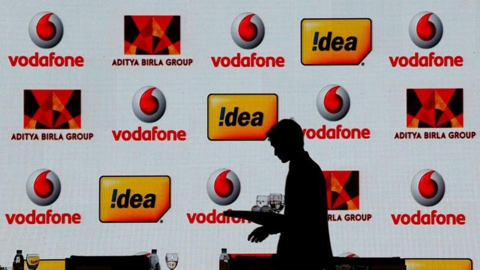 A hotel employee clears a table after Vodafone Group and Idea Cellular news conference in Mumbai.