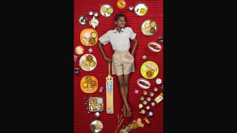 Chetan Menge, 10, Mumbai,  India. Chetan's father is a night watchman and his mother owns a beauty parlour. The family eats their meals in front of the little TV that is the centre-piece of their small home.  (Gregg Segal)
