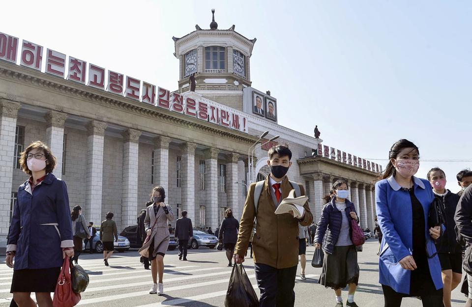 People wearing protective face masks walk amid concerns over the Covid-19 in front of Pyongyang Station in Pyongyang