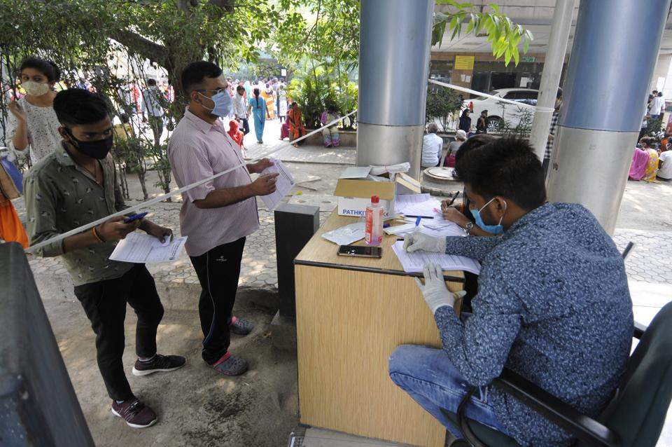 A health worker registers people for coronavirus test, at Sector 30 District Hospital, in Noida (Photo by Sunil Ghosh / Hindustan Times)
