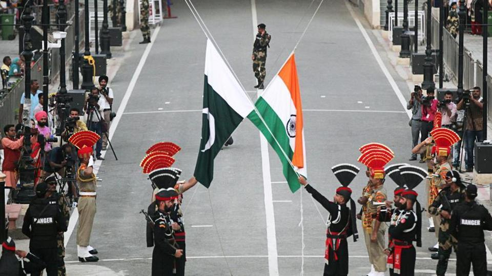 Pakistani Rangers (wearing black uniforms) and Indian Border Security Force (BSF) officers lower their national flags during parade on the Pakistan's 72nd Independence Day, at the Pakistan-India joint check-post at Wagah border,  August 14, 2019.