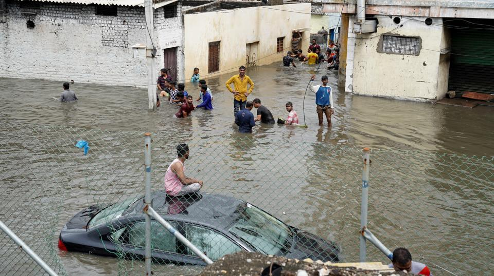 People are seen in a flooded residential area after heavy rainfall in Hyderabad on October 14, 2020.
