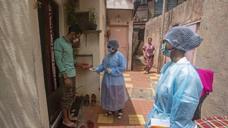 Health workers are seen during a door to door screening for the coronavirus disease (Covid-19) in a slum near Dandekar bridge in Pune in this file photo.
