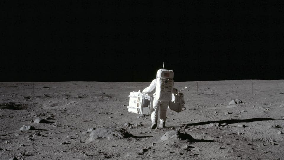 In this July 20, 1969 photo made available by NASA, lunar module pilot Buzz Aldrin carries a seismic experiments package in his left hand and the Laser Ranging Retroreflector to the deployment area on the surface of the moon at Tranquility Base. On Tuesday, Oct. 13, 2020, NASA released a set of guidelines for its Artemis moon-landing program, based on the 1967 Outer Space Treaty and other agreements.