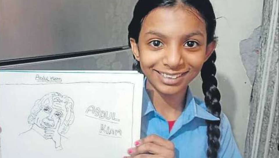 A student showing a portrait made by her to pay tribute to Kalam.