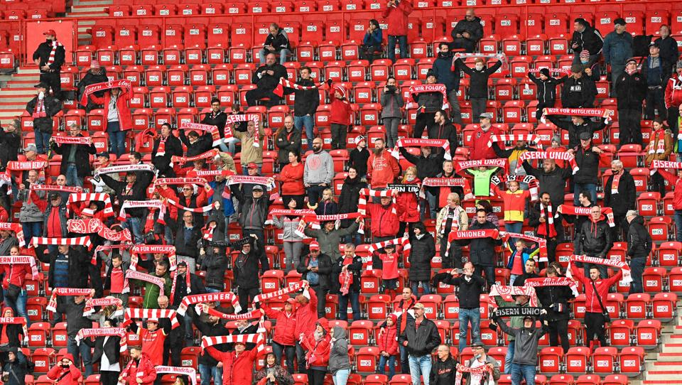 Supporters of German first division Bundesliga 1 FC Union Berlin cheer for their team on the stands during a friendly test football match between 1 FC Union Berlin and second division club Hannover 96 in Berlin on October 8, 2020. (Photo by Tobias Schwarz / AFP) / DFL REGULATIONS PROHIBIT ANY USE OF PHOTOGRAPHS AS IMAGE SEQUENCES AND/OR QUASI-VIDEO