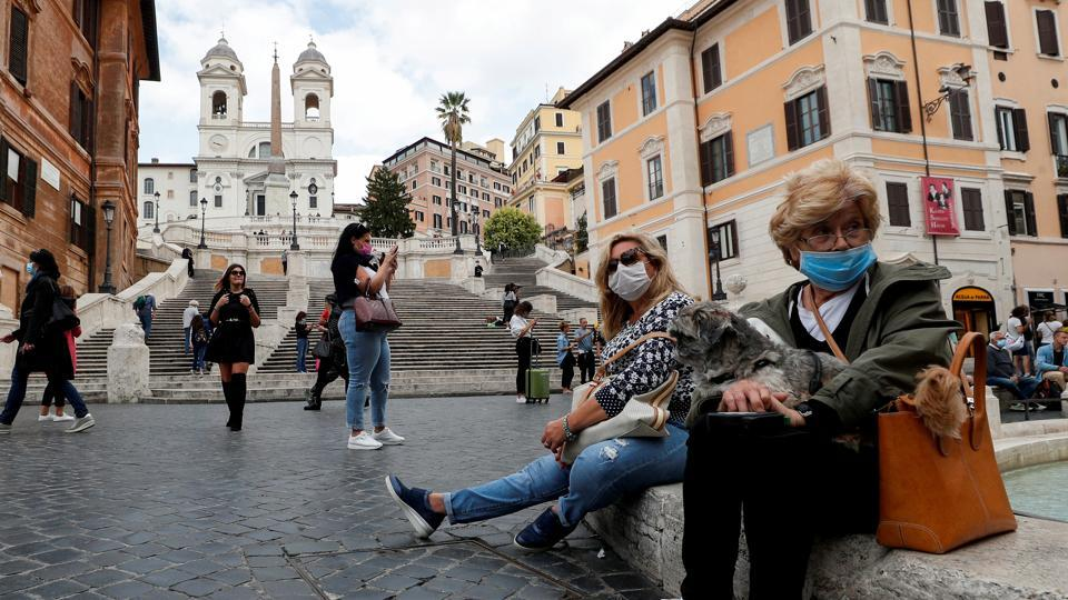 Women wearing face masks sit next to the Spanish Steps, as local authorities in the Italian capital Rome order face coverings to be worn at all times out of doors in an effort to counter rising coronavirus infections, in Rome, Italy October 2, 2020.