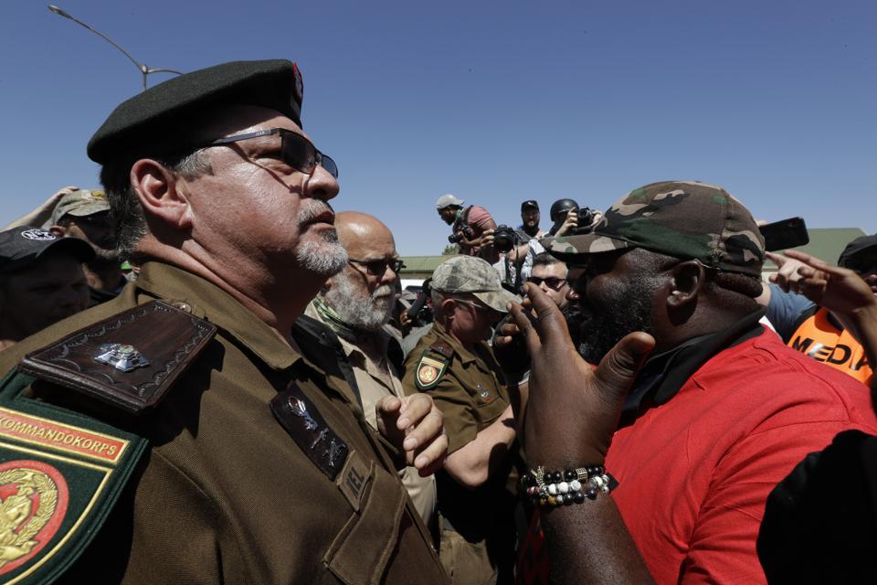 The killing of a white farmer allegedly by two black men in South Africa has stoked racial tensions. In picture - A member of the Economic Freedom Fighters, right, confront white farmers, left, during protest outside the magistrates court in Senekal, South Africa