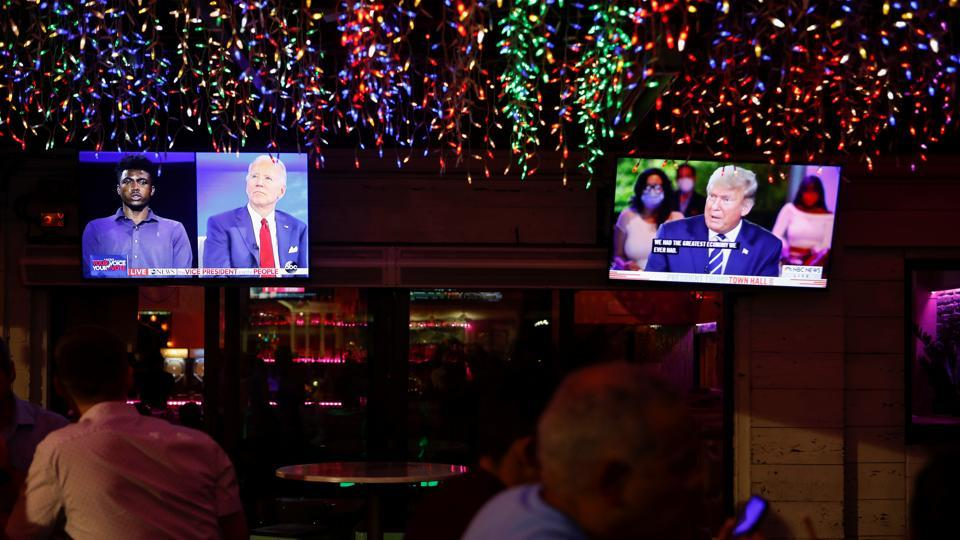 The dual town halls of US Democratic presidential candidate Joe Biden and US President Donald Trump, who are both running in the 2020 US presidential election, are seen on television monitors at Luv Child restaurant ahead of the election in Tampa, Florida.