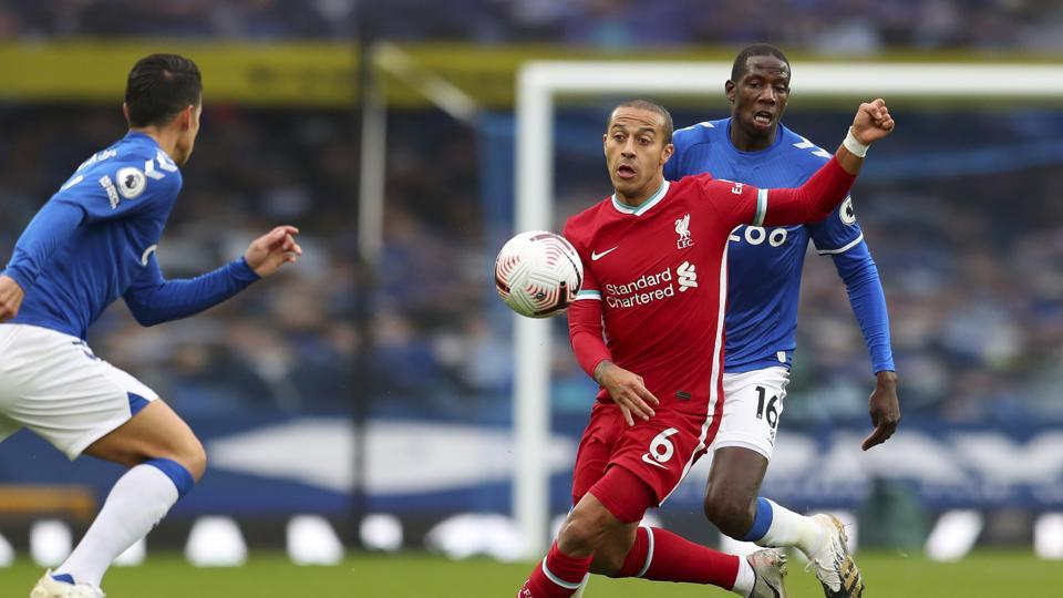 Liverpool's Thiago, 6, competes for the ball with Everton's Abdoulaye Doucoure, right, during the English Premier League soccer match between Everton and Liverpool at Goodison Park stadium, in Liverpool, England, Saturday, Oct. 17, 2020. (Cath Ivill/Pool via AP)