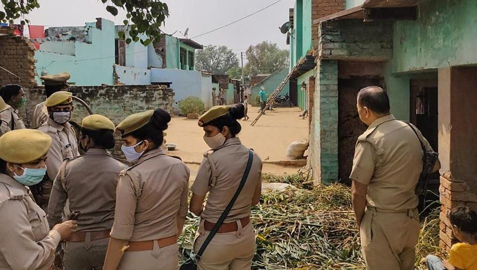 Police personnel stand guard as CBI officials (not visible in picture) investigate the Hathras case.
