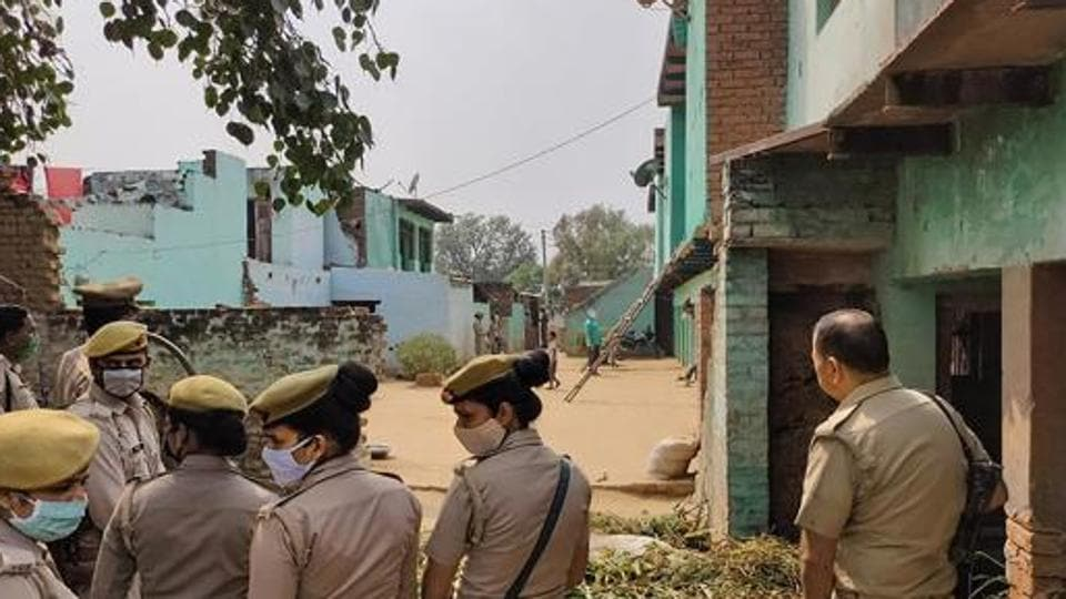 Police personnel stand guard as CBI officials (unseen) investigate the case of a 19-year-old Dalit woman who died after being allegedly gang-raped, inHathras.