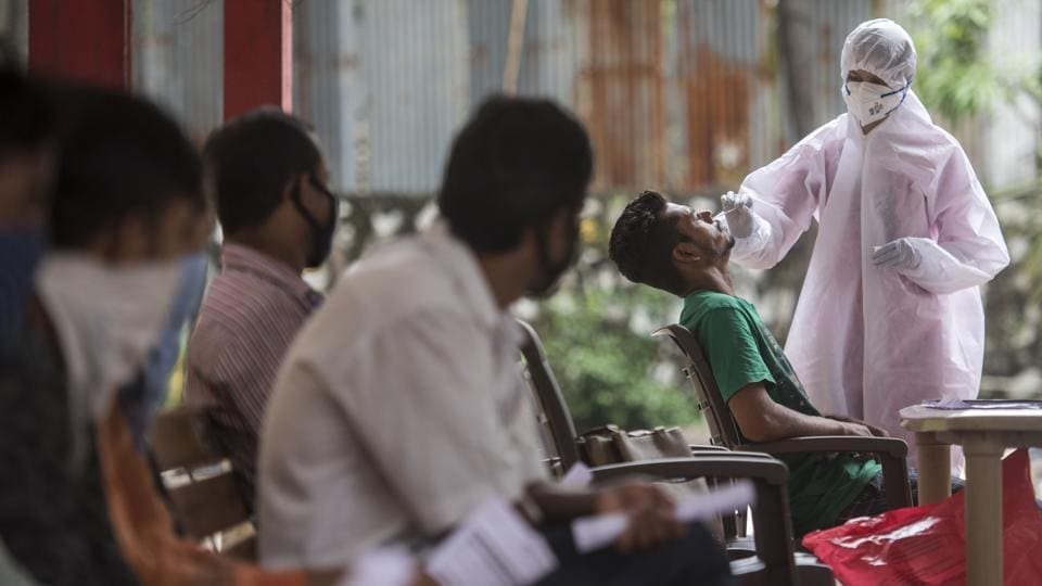 A health worker collects a swab sample from a man for Covid-19 test at Goregaon (E) in Mumbai on October 16. The cases of the coronavirus disease (Covid-19) have shown signs of decline across India in the last week as the number of fresh infections did not cross the 70,000 mark since October 12. (Satyabrata Tripathy / HT Photo)