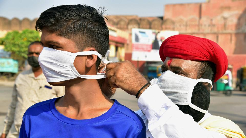 A social worker puts a face mask on a boy in the wake of coronavirus pandemic during an awareness drive, in Bikaner.