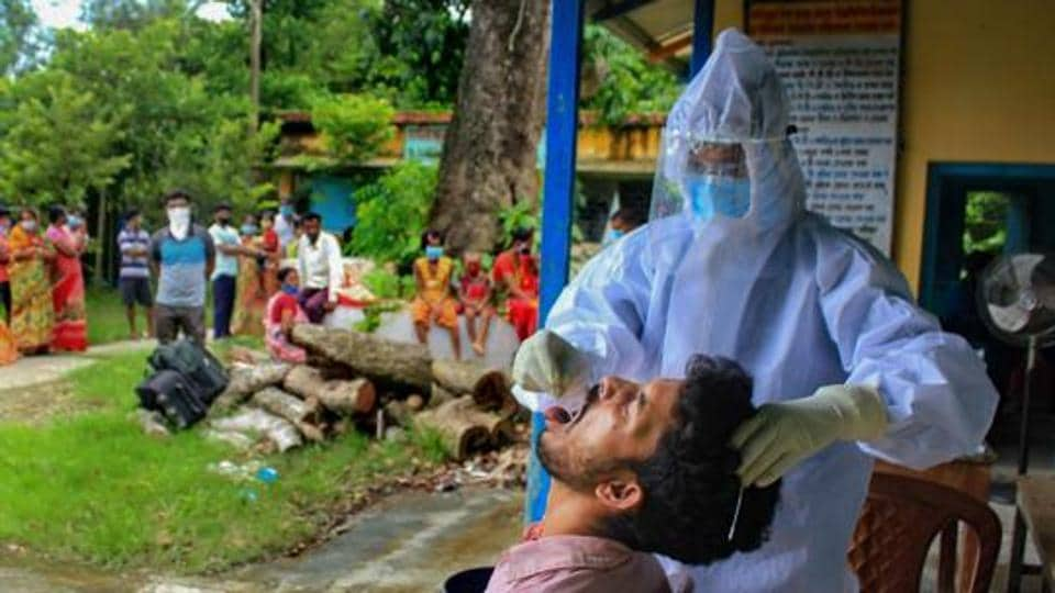 A health worker collects swab sample of a villager for Covid-19 test in Manipur.