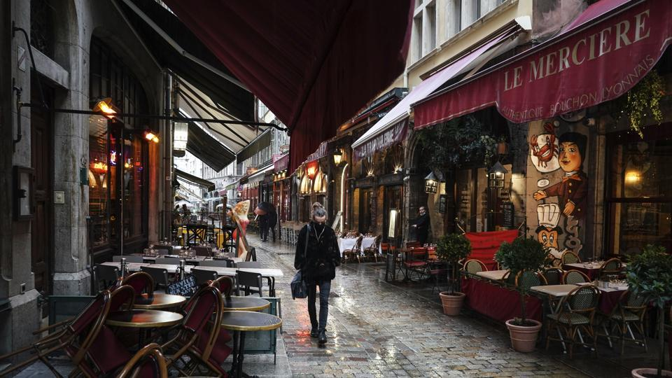 A woman walks by empty restaurants in the center of Lyon, central France.