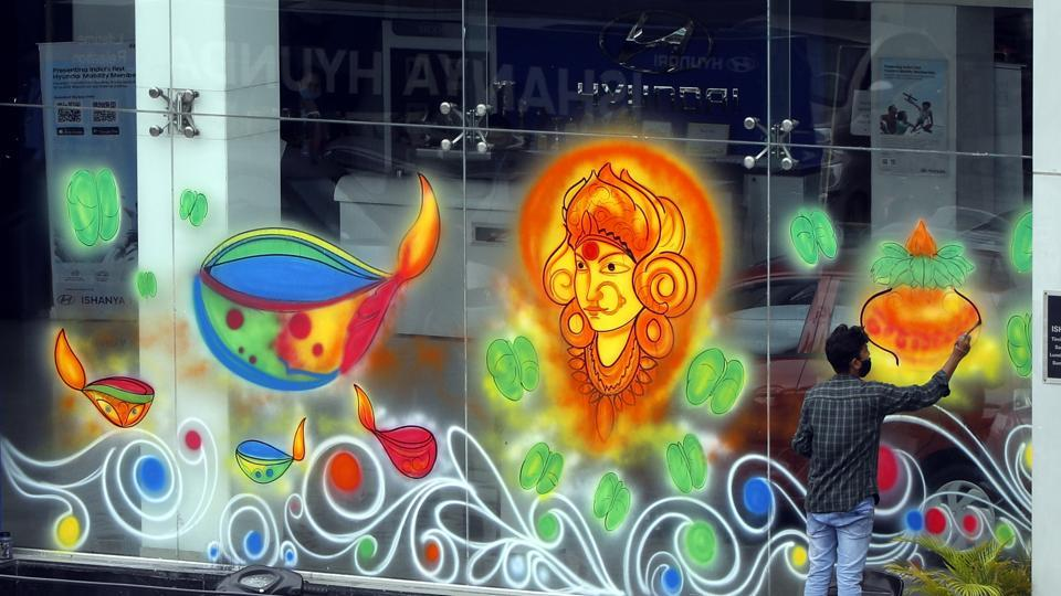 A man paints festive designs on the occasion of Navratri outside a vehicle showroom at Satara road in Pune on Friday.