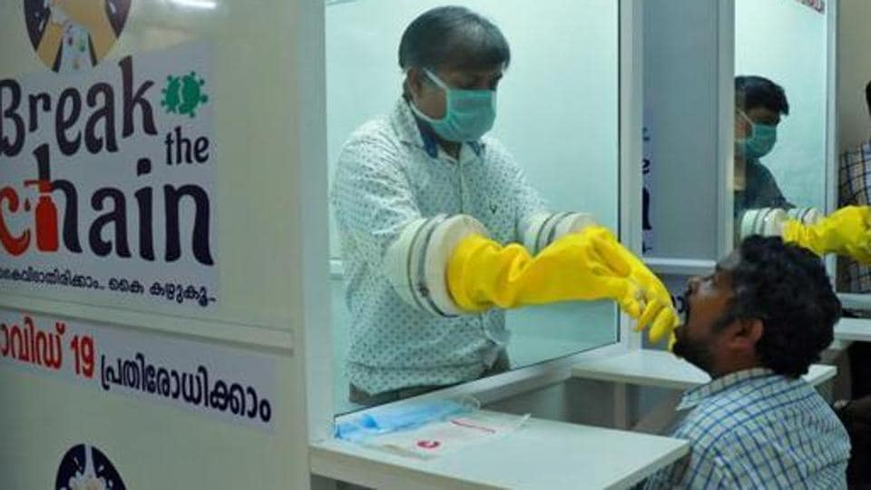 Medical staff members of a government-run medical college collect swabs from people to test for Covid-19 at a Walk-In Sample Kiosk (WISK) in Ernakulam, Kerala.