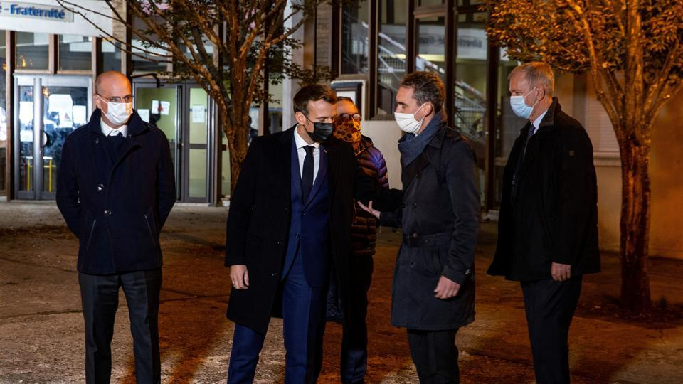 French President Emmanuel Macron and French Education Minister Jean-Michel Blanquer talk with officials as they visit the scene of a stabbing attack in the Conflans-Sainte-Honorine suburb of Paris, France.