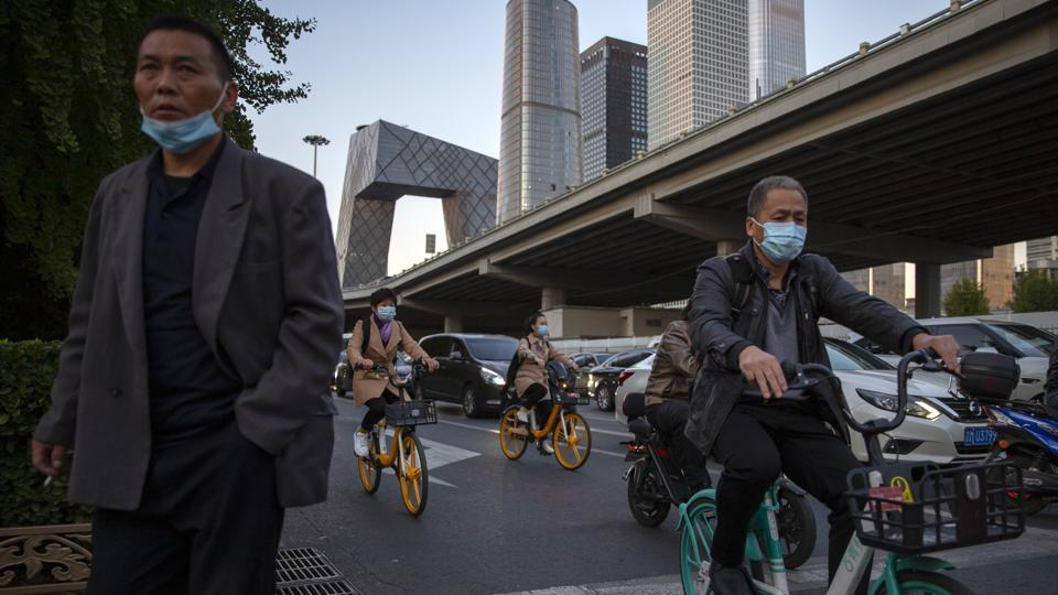 Commuters wearing face masks to protect against the coronavirus wait at an inteserction in the central business district in Beijing, Friday, Oct. 16, 2020. Authorities have completed tests on more than 10 million people in the northern Chinese port city of Qingdao after a hospital outbreak there blamed on
