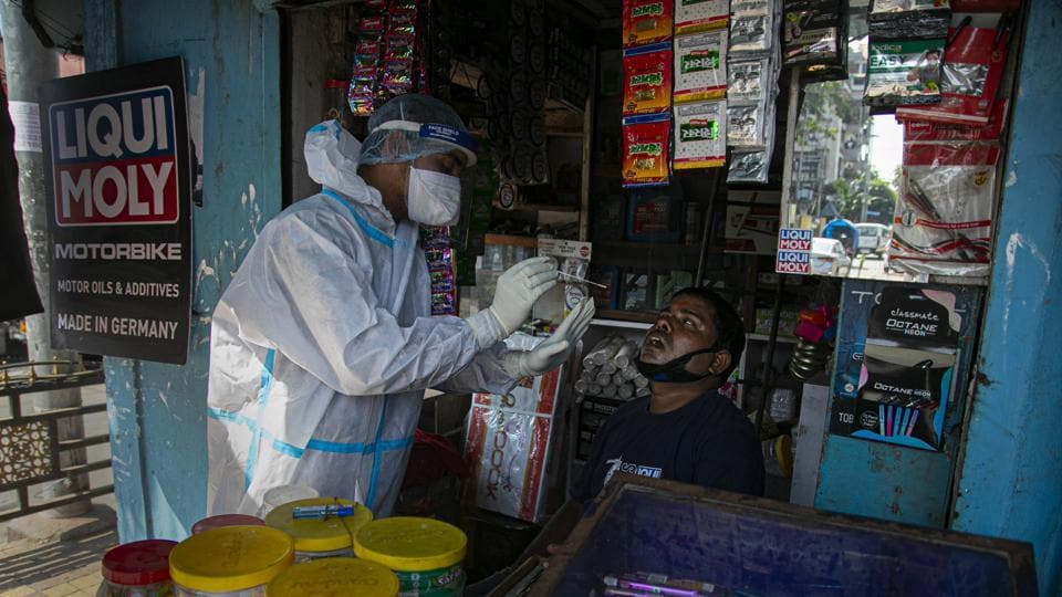 A health worker takes a nasal swab sample of a shopkeeper during random testing for Covid-19 in a market in Guwahati, Assam on October 16, 2020.