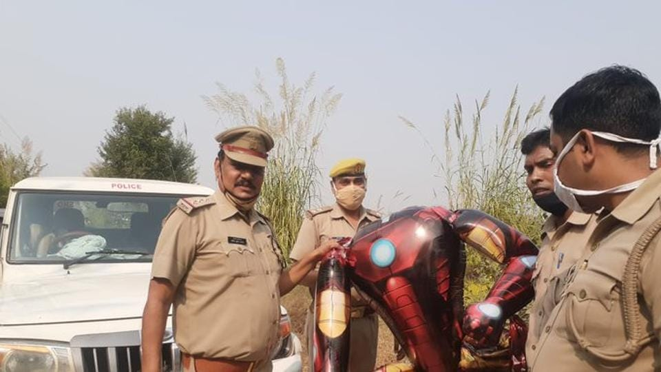 The image shows the police officials holding the Ironman-shaped ballon.