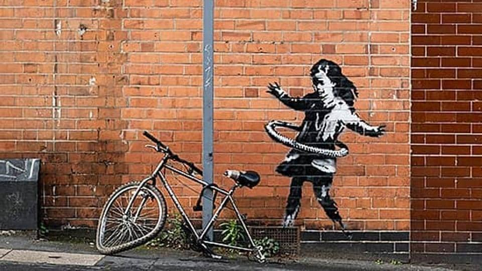 The work appeared on Tuesday on the red brick wall of a beauty salon, next to a bicycle that was locked to a metal signpost and missing its back wheel.