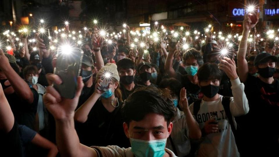 Pro-democracy protesters shine their mobile phone lights during an anti-government protest, in Bangkok, Thailand.