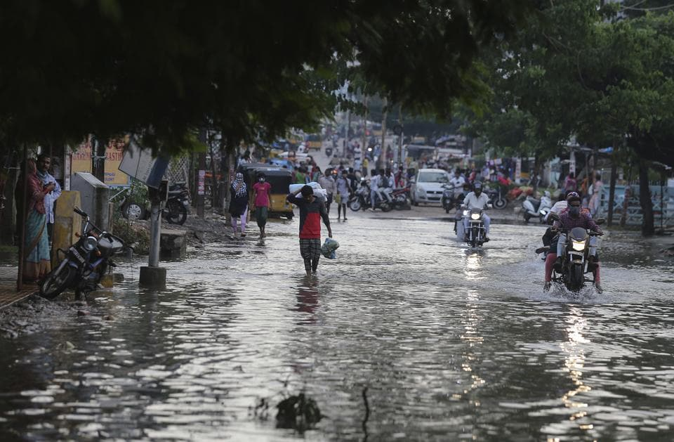 Commuters wade through receding floodwaters after heavy rainfall in Hyderabad on October 15.