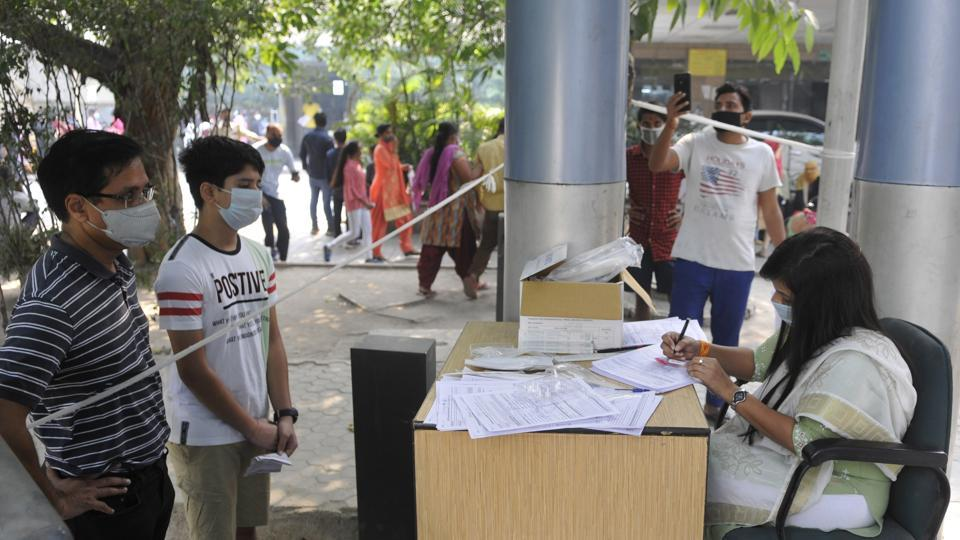 A health worker registers people for coronavirus test at Sector 30 District Hospital in Noida.