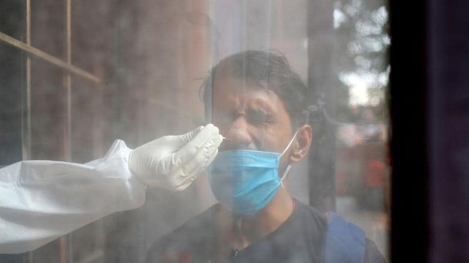 A man reacts as a healthcare worker collects a swab sample at a testing centre, in New Delhi.