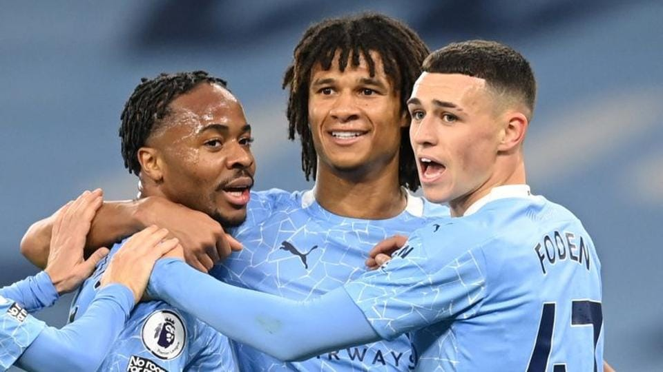 Manchester City's Raheem Sterling celebrates scoring their first goal with Phil Foden and Nathan Ake.