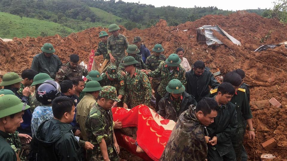 This picture taken on October 18, 2020 and released by the Vietnam News Agency on October 18, 2020 shows military personnel carrying a body recovered from the site of a landslide in central Vietnam's Quang Tri province. (Photo by STR / Vietnam News Agency / AFP)