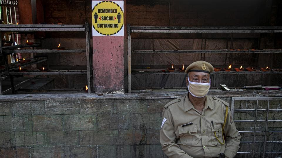 A security person sits wearing a mask outside a temple in Guwahati.
