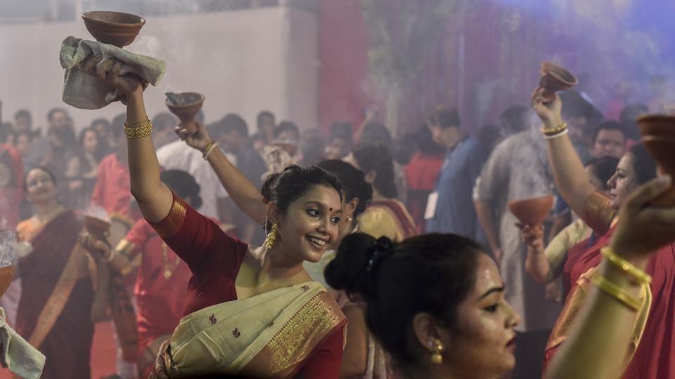 Women perform Dhunuchi dance during Durga Puja at Shivaji Park in Mumbai on October 2018
