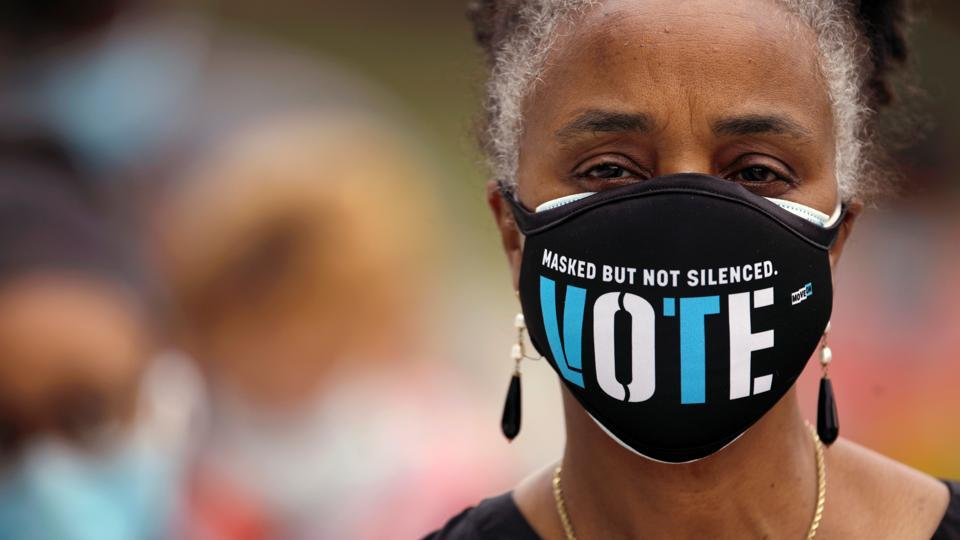 A woman wearing a mask with a message urging voter participation waits in line to enter a polling station on the first day of the state's in-person early voting for the general election in Durham, North Carolina on October 15. More than 17 million Americans have already cast ballots in the 2020 election, a figure that represents 12% of all the votes cast in the 2016 presidential election. (Jonathan Drake / REUTERS)